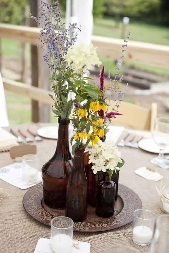 Lindo centro de mesa com garrafas de vidro